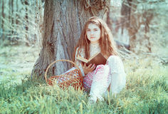 Flicka som läser en bok under ett träd Royaltyfria Foton