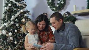 Flicka som läser en bok under julgranen lager videofilmer