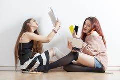 Flicka som läser en bok VS flickan som använder massor av mobiler Arkivbild