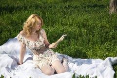 Flicka som läser ett boksammanträde på gräset arkivfoto