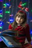 Flicka som läser julboken Royaltyfria Foton
