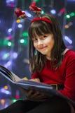 Flicka som läser julboken Fotografering för Bildbyråer