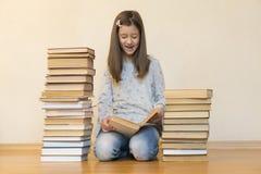 Flicka som l?ser ett boksammantr?de p? golvet i en l?genhet Gullig flickal?sebok hemma utbildning och skolabegrepp - lite fotografering för bildbyråer