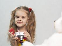 Flickan tar fotoet av den digitala kameran för nallen Arkivfoto