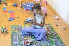 Flicka som leker i rummet flicka 8 gamla år på golvet med leksaker royaltyfria bilder
