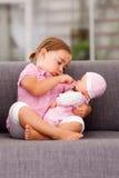 Flicka som leker med dockan Royaltyfri Bild