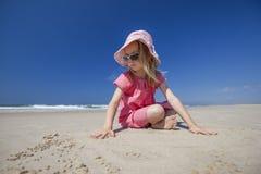 Flicka som leker på sandig strand Arkivbild
