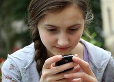 Flicka som leker på telefonen Fotografering för Bildbyråer