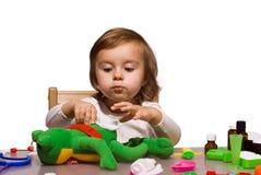 Flicka som leker som doktor med henne toys 1 arkivbilder