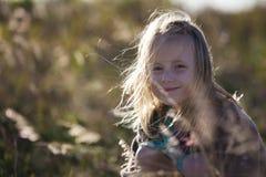Flicka som ler bland gräs Fotografering för Bildbyråer