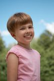 Flicka som ler i en parkera på en bakgrund av himlen Royaltyfria Bilder