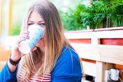 Flicka som ler i ett kafé Söt fyllig flicka Kvinna som dricker från en pappers- kopp i ett kafé Royaltyfri Foto
