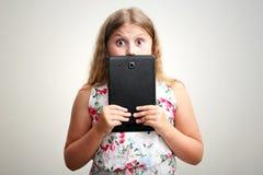 Flicka som ler och förvånas med minnestavladatoren Arkivbild