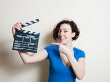 Flicka som ler peka ut filmclapperen på vit bakgrund Royaltyfri Bild