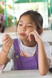 Flicka som ler sammanträde på en vit tabell Arkivbilder