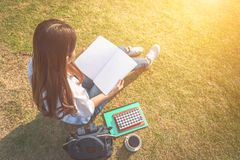 Flicka som ligger i gräs som läser en bok Avsiktligt tonat royaltyfria foton