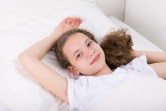 Flicka som ligger i säng som drömmer, hand bak huvudet, vit bakgrund Arkivfoto