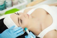 Flicka som ligger i skönhetbrunnsorten som tycker om hudterapi genom att använda aktuell tre Royaltyfri Fotografi