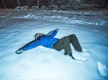 Flicka som ligger i snönatt Royaltyfri Foto