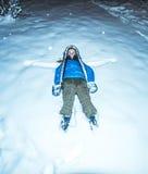 Flicka som ligger i snönatt Arkivfoto