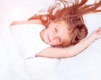 Flicka som ligger i vit säng Royaltyfria Foton