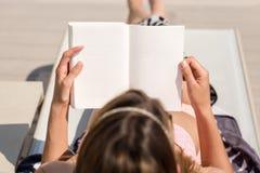 Flicka som ligger läsa en bok arkivfoto