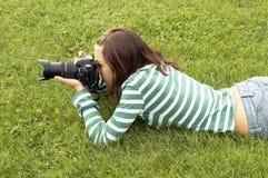 Flicka som ligger med fotokameran arkivfoto