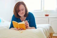 Flicka som ligger på baden och skriver in i dagboken Royaltyfri Fotografi