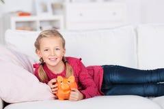 Flicka som ligger på den hållande spargrisen för soffa Royaltyfri Foto