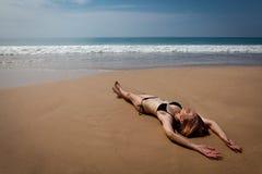 Flicka som ligger på den tropiska stranden som solbadar Arkivbild