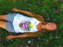 Flicka som ligger på det gröna gräset i sommar Äng med växt av släktet Trifolium lon Fotografering för Bildbyråer