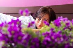 Flicka som ligger på en säng med blommor Royaltyfri Bild