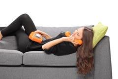 Flicka som ligger på en soffa och talar på tappningtelefonen Arkivbilder