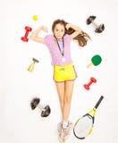 Flicka som ligger på golv med uppsättningen av sportutrustning Arkivbild