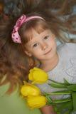 Flicka som ligger på golvet med tulpan som en gåva för moder royaltyfria bilder