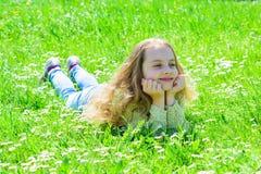 Flicka som ligger på gräs på grassplot, grön bakgrund Barnet tycker om soligt väder för våren, medan ligga på ängen Fred och royaltyfri bild