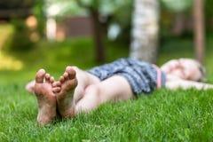 Flicka som ligger på gräset, fot på förgrund Arkivbilder
