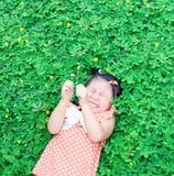 Flicka som ligger på gräsmattan Fotografering för Bildbyråer