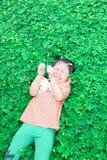 Flicka som ligger på gräsmattan Arkivfoto