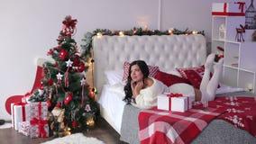 Flicka som ligger på sängen med en julgåva stock video