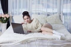 Flicka som ligger på sängen och arbetet med en bärbar dator Fotografering för Bildbyråer