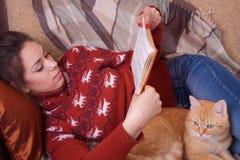 Flicka som ligger på soffan med röd katt och läsning a Arkivfoton