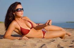 Flicka som ligger på stranden Arkivbilder