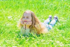Flicka som ligger p? gr?s p? grassplot, gr?n bakgrund Barnet tycker om soligt v?der f?r v?ren, medan ligga p? ?ngen Fred och royaltyfria foton