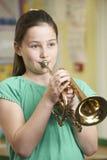 Flicka som lär att spela trumpeten i skolamusikkurs Arkivbild