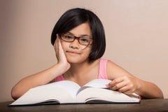 flicka som läser den stora boken Royaltyfri Fotografi