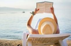 Flicka som läser en bok, i sunbed Arkivfoto