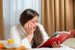Flicka som läser en intressant tidskrift på säng Royaltyfri Bild