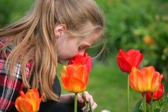 Flicka som luktar blommor i trädgården Arkivfoton