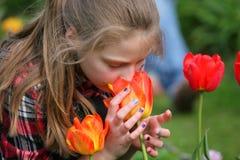 Flicka som luktar blommor i trädgården Arkivfoto